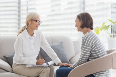 smiling female therapist happy talking to her client
