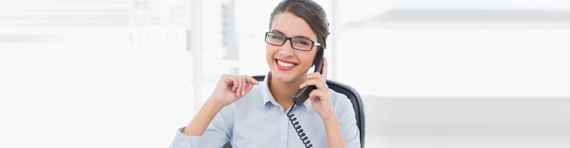 delighted classy brown haired professional woman answering the telephone